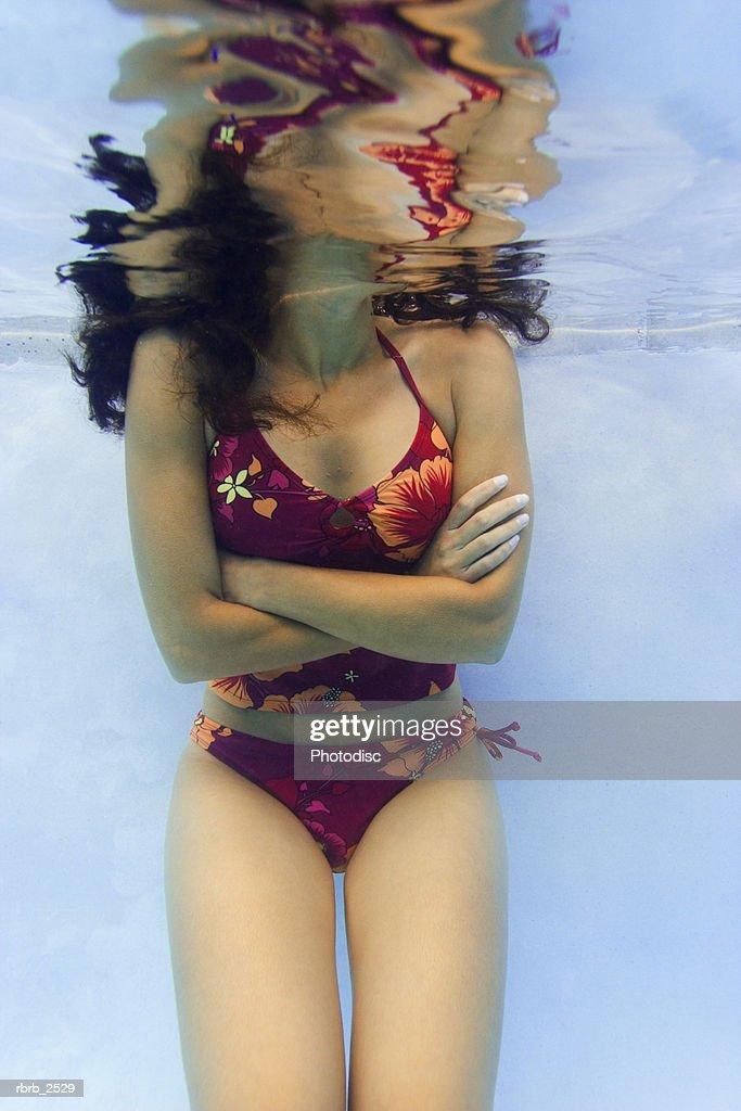 underwater shot of a young adult female as she stands in a pool with her head above water : Foto de stock