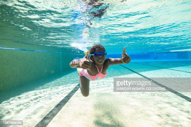 Underwater shot of Indigenous Australian Aboriginal girl in public swimming pool gesturing thumbs up