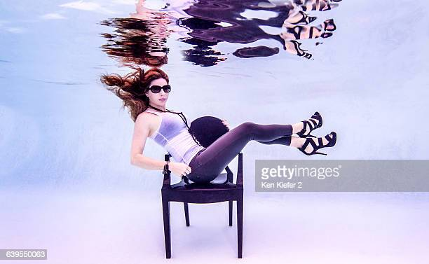 Underwater side view of mid adult woman wearing high heels and sunglasses in swimming pool sitting on chair looking at camera