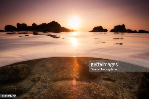 Underwater split level of rocky seashore at sunset