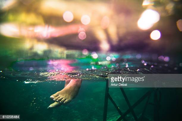 Underwater view of a feet girl sitting on beach dock contemplating the view in the Mediterranean Sea Costa brava during summer vacations.