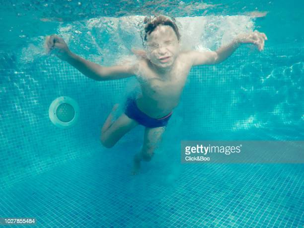 Underwater view of a five years old boy in a blue swim suit