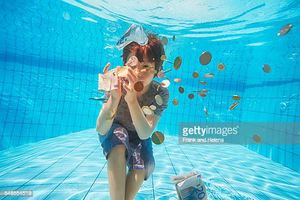 Underwater view of boy grabbing euro currency in swimming pool