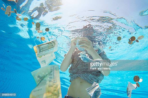 Underwater view of boy in swimming pool grabbing euro currency