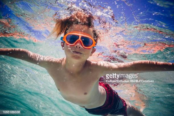 underwater view of boy swimming underwater in sea, portrait - knaben in badehosen stock-fotos und bilder