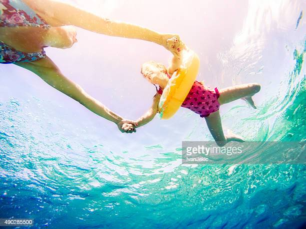 Underwater view of family swiming and holding hands in sea