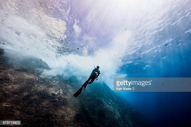 underwater view of female diver exploring roca partida pinnacle, socorro, baja california, mexico - underwater diving stock pictures, royalty-free photos & images