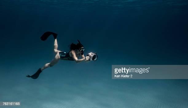 Underwater view of female free diver with underwater camera, Bimini, Bahamas