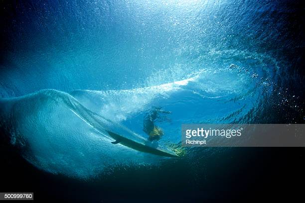 Underwater view of longboard surfer on a wave