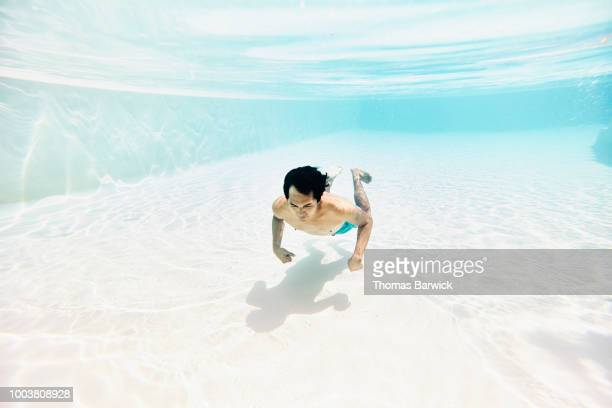 Underwater view of man swimming underwater in pool