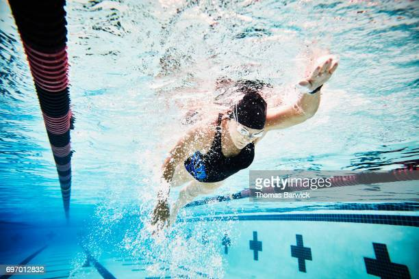 Underwater view of mature female athlete swimming during morning workout