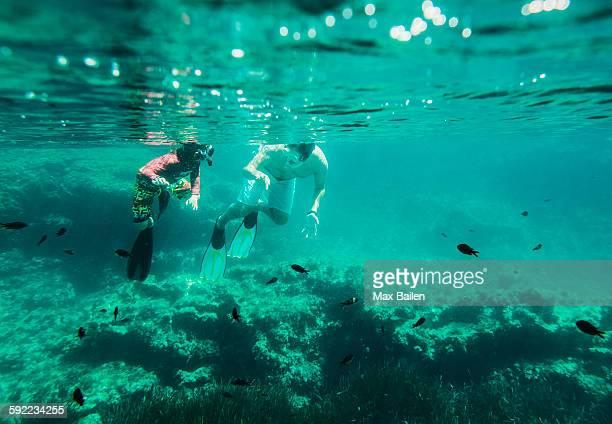 Underwater view of mature man and son sea snorkeling, Menorca, Balearic islands, Spain