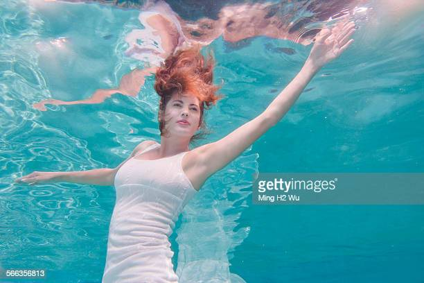 Underwater view of mixed race woman in dress swimming in pool