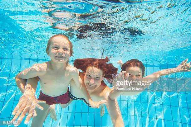Underwater view of mother and two sons diving in swimming pool