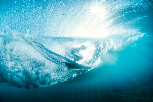 Underwater view of person surfboarding on wave - gettyimageskorea