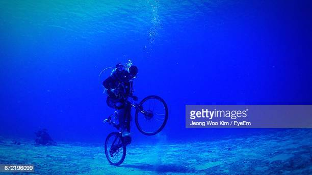 Underwater View Of Scuba Diver On A Bicycle