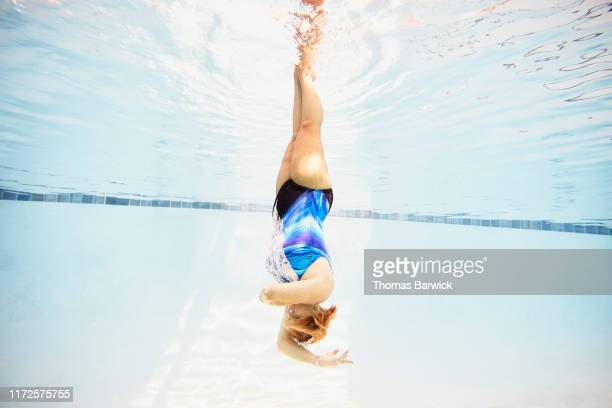 underwater view of senior female synchronized swimmer upside down during routine - artistic swimming stock pictures, royalty-free photos & images