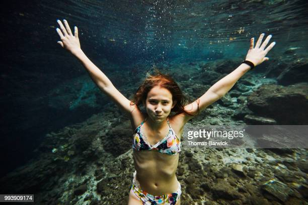 Underwater view of smiling girl holding breath while swimming underwater