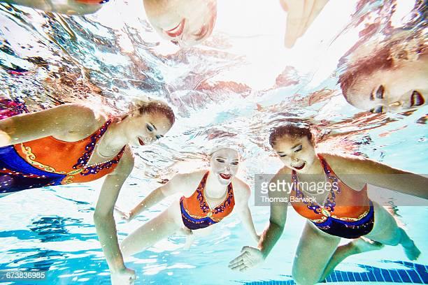 Underwater view of smiling synchronized swim team