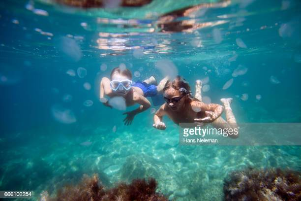 underwater view of two kids diving - bikini bottom stock pictures, royalty-free photos & images