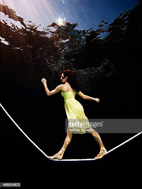 Underwater view of woman balancing on tightrope