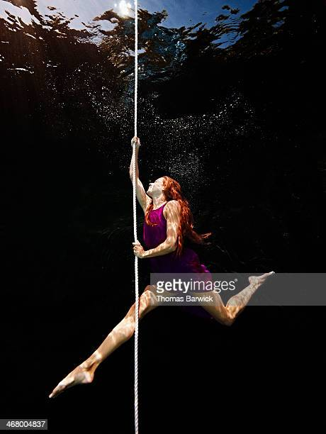 Underwater view of woman climbing up rope