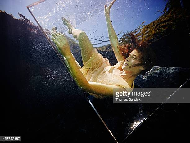 Underwater view of woman falling in glass box