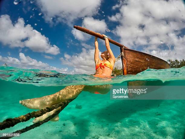Underwater view of woman hanging onto wooden boat