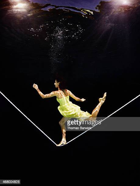 Underwater view of woman running on tightrope