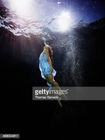 Underwater View Of Woman Swimming To Surface High Res