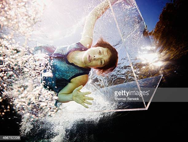Underwater view of woman trapped in glass box