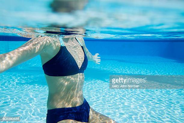 Underwater view of young woman in swimming pool, neck down wearing bikini