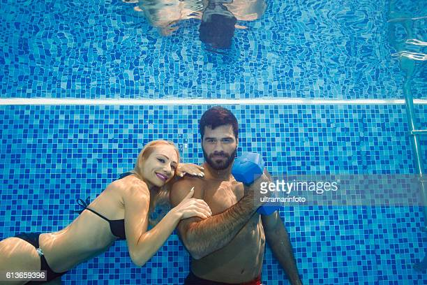 Underwater  Women and men training  with dumbbells  in swimming pool