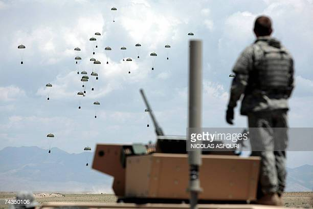 A US soldier looks on as a C117 plane is drops food water and other supplies onto a landing zone at an undisclosed location in the Ghazni province of...