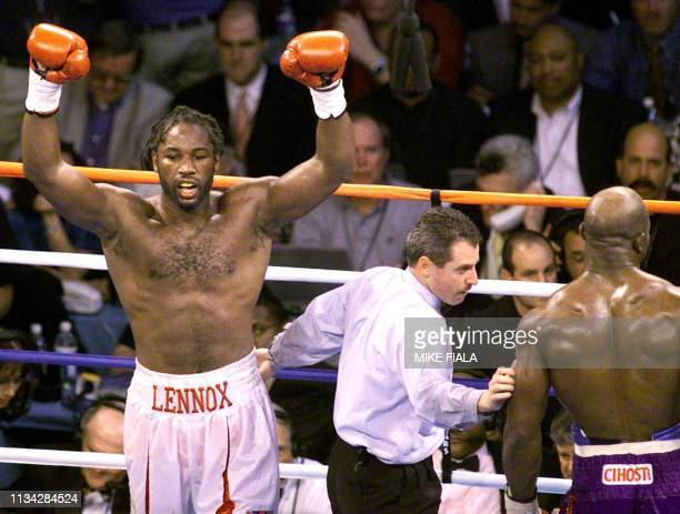 Undisputed world heavyweight Champion Lennox Lewis from Great Britain celebrates as referee Mitch Halpern leads American Evander Holyfield to his...