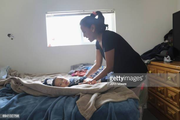 Undocumented immigrant activist Jeanette Vizuerra changes her grandson's diaper on June 6 2017 in Denver Colorado Vizguerra was given a temporary...