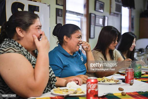 Undocumented immigrant Eva Carranza second left laughs along with other community members during Thanksgiving lunch at the nonprofit Arise which...