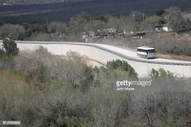 Undocumented immigrant families are bussed along a levee that forms part of the USMexico border fence while in route to a US Border Patrol processing...