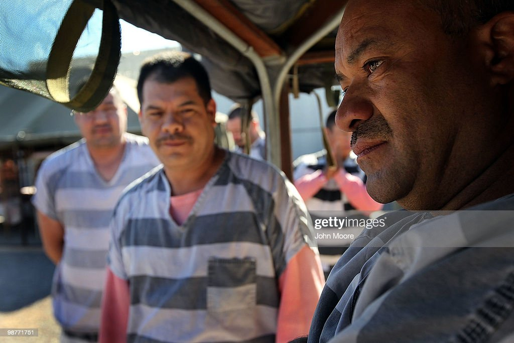 Undocumented immigrant Jose Hechavaria (R), 43, stands with fellow prisoners in the yard of the Maricopa County Tent City Jail on April 30, 2010 in Phoenix, Arizona. Hechavaria, a 13-year resident of Arizona, said he was arrested by sheriff's deputies on a DUI charge and then held because of his illegal immigration statues. Some 200 undocumented immigrants are currently serving time in the facility. The controversial jail is run by Maricopa County Sheriff Joe Arpaio, who has been an outspoken critic of illegal immigration and a supporter of Arizona's new tough immigration law. Prisoners at the facility are fed twice a day, sleep in non-airconditioned tents and are issued striped prison uniforms and pink underwear and socks.