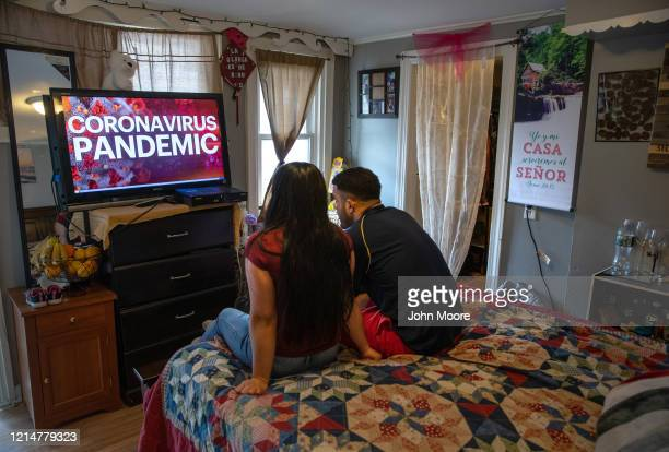 Undocumented immigrant Juana from El Salvador and her husband Saul from Honduras watch local news in their one-room apartment on March 25, 2020 in...