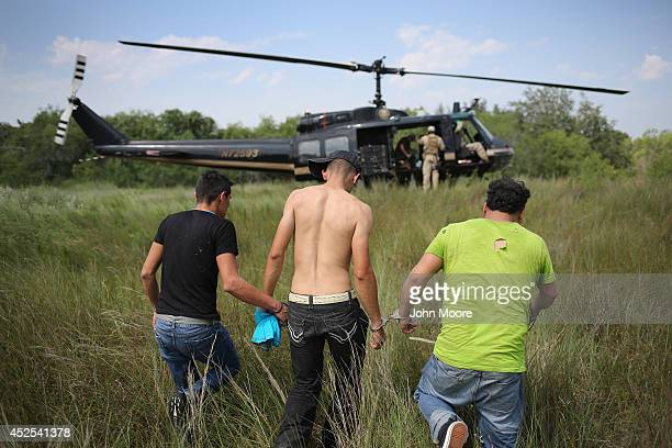 Undocumented immigrants await transport to a US Customs and Border Protection processing center after being detained on July 22 2014 near Falfurrias...