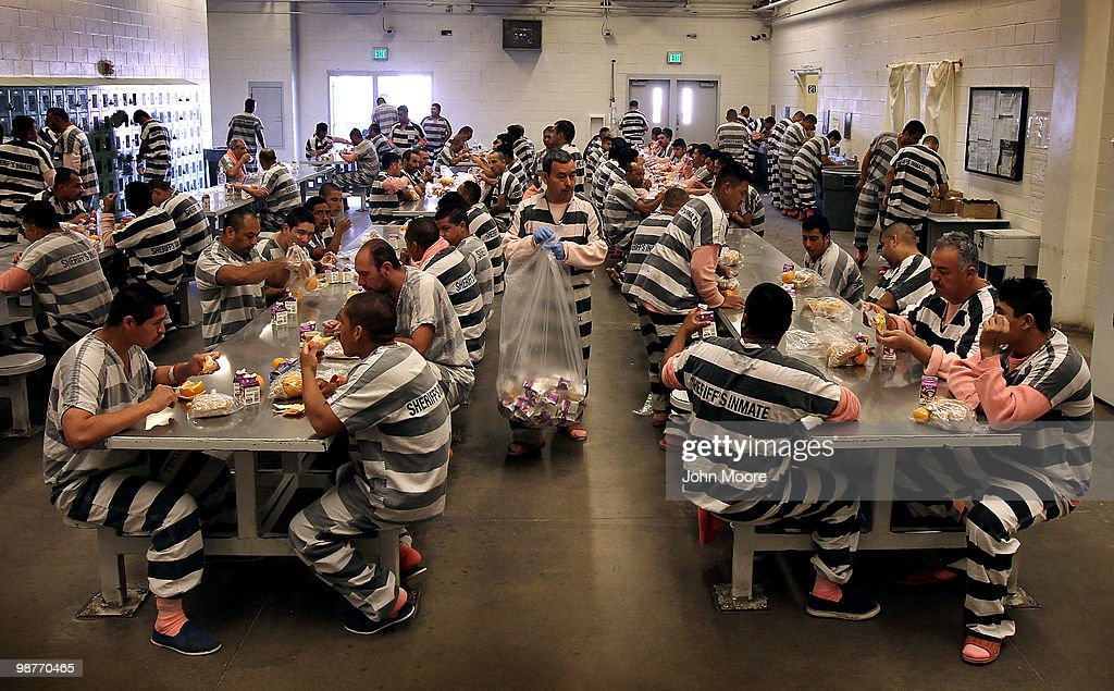 Undocumented immigrants 'brunch' in the Maricopa County 'Tent City Jail' on April 30, 2010 in Phoenix, Arizona. Some 200 undocumented immigrants are currently serving time in the facility, and most will be deported to Mexico after serving their sentence. The controversial jail is run by Maricopa County Sheriff Joe Arpaio, who has been an outspoken critic of illegal immigration and a supporter of Arizona's new tough immigration law. Prisoners at the facility are fed twice a day, sleep in non-airconditioned tents and are issued striped prison uniforms and pink underwear and socks.