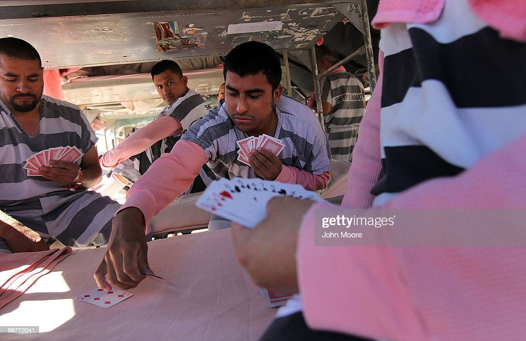 Undocumented immigrants play cards in their tent at the Maricopa County Tent City Jail on April 30, 2010 in Phoenix, Arizona. Some 200 undocumented immigrants are currently serving time in the facility, and most will be deported to Mexico after serving their sentence. The controversial jail is run by Maricopa County Sheriff Joe Arpaio, who has been an outspoken critic of illegal immigration and a supporter of Arizona's new tough immigration law. Prisoners at the facility are fed twice a day, sleep in non-airconditioned tents and are issued striped prison uniforms and pink underwear and socks.