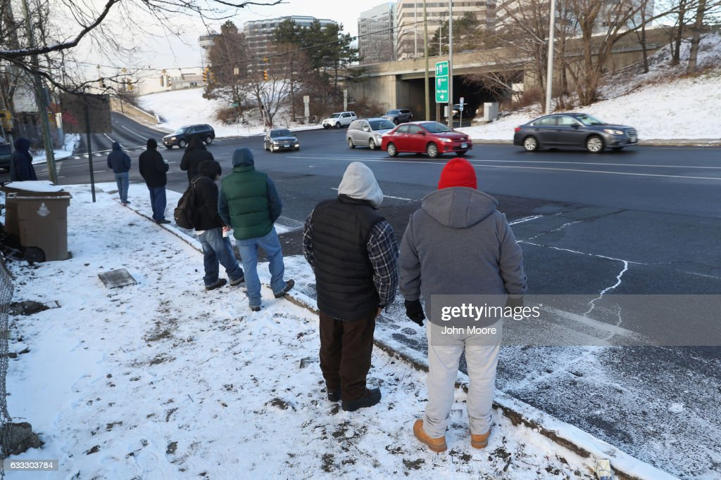 Undocumented immigrants wait for work along a city street on February 1, 2017 in Stamford, Connecticut. The city of Stamford has an official zone for employers to pick up day laborers, although many prefer to stand by nearby businesses for warmth and greater visibility to employers. Stamford, CT is located in Fairfield County, considered a 'sanctuary county' for not reporting undocumented immigrants to federal authorities.