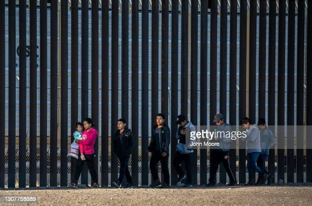 Undocumented immigrants walk along the U.S.-Mexico border wall after they ran across the shallow Rio Grande into El Paso on March 17, 2021 in Ciudad...