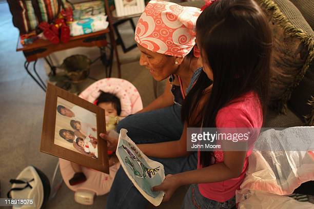 Undocumented Mexican immigrant Jeanette Vizguerra looks over a family portrait with her daughter Luna while packing up belongings in her apartment on...