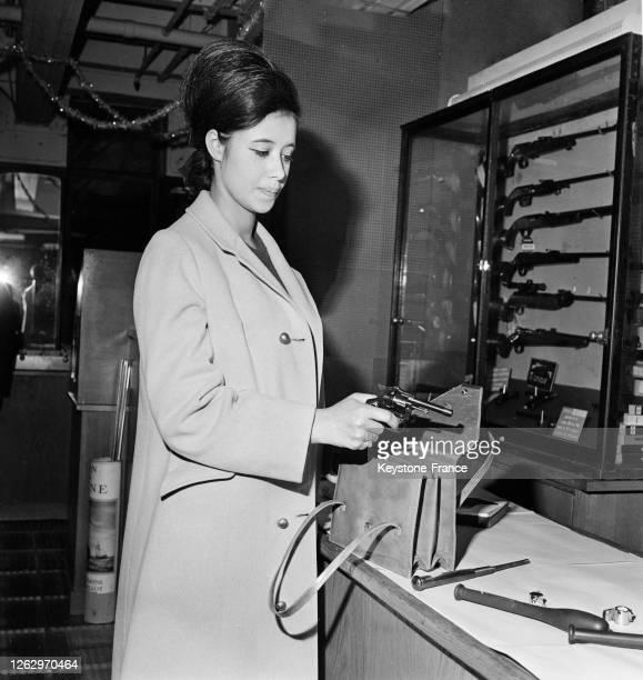 Une acheteuse essaie le minirevolver minigadget d'autodéfense à Paris France le 23 novembre 1966
