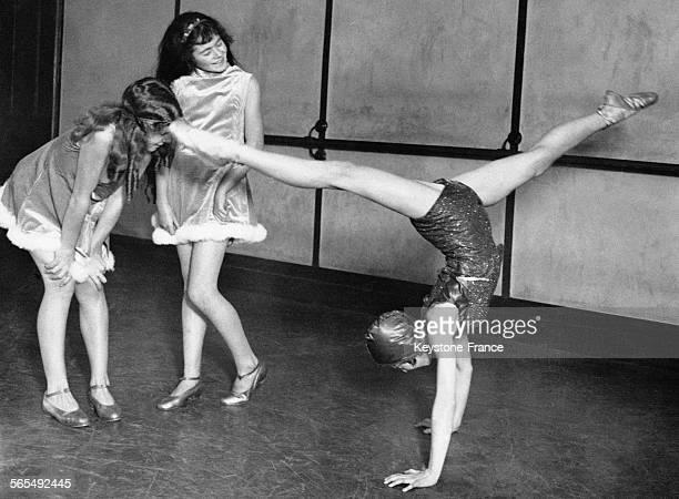 Une acrobate sur les mains et jambes en grand écart devant deux collègues pendant la répétition d'un spectacle auquel assistera le Prince de Galles...