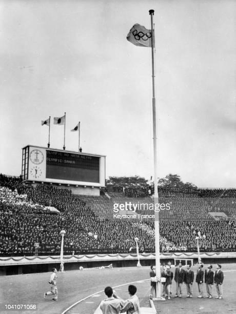 Une ancienne équipe olympique japonaise hisse le drapeau olympique dans le stade Meiji en présence d'écoliers japonais le 28 septembre 1964 à Tokyo...