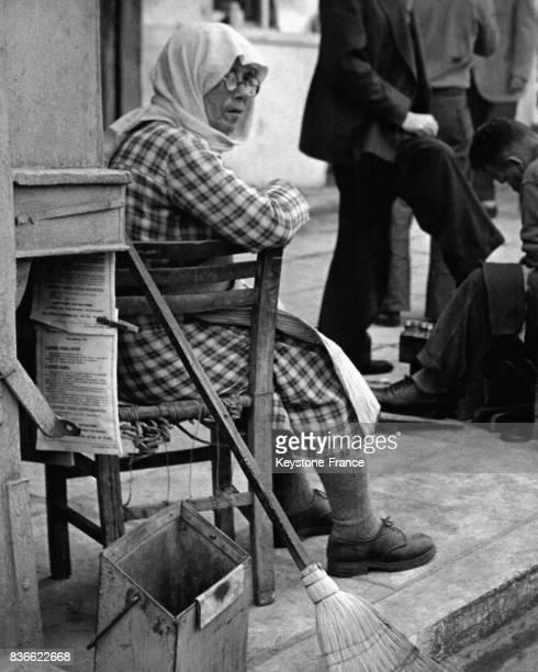 Une balayeuse municipale assise sur une chaise à côté de son balai à Athènes GRèce